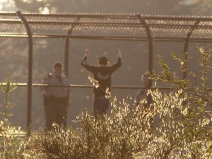 The man is hanging onto the outside of the pedestrian overpass